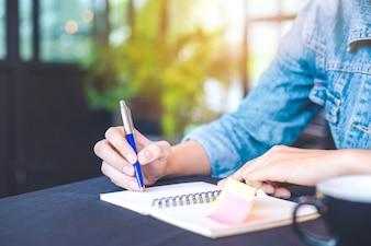 A mão da mulher está escrevendo em uma almofada de nota com uma pena no escritório.
