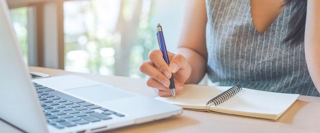 A mão da mulher está escrevendo no bloco de notas com a pena no escritório.