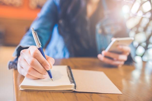 A mão da mulher está escrevendo no bloco de notas espiral vazio com uma pena e usa um smartphone.