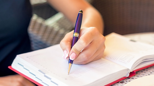 A mão da mulher está escrevendo o plano de negócios no pequeno caderno na área ao ar livre no café.