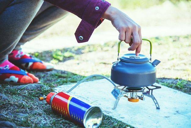 A mão da mulher está guardando uma chaleira. colocado em um fogão a gás de piquenique.