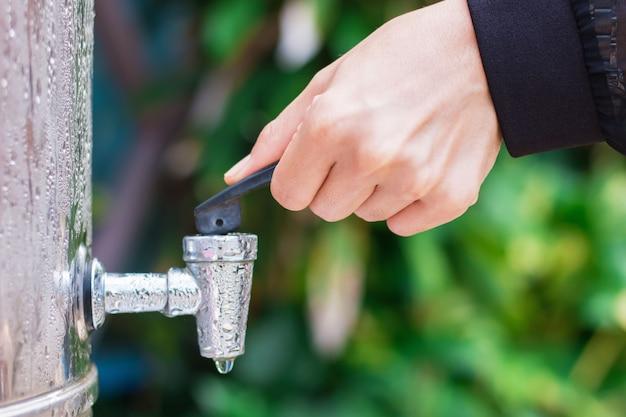 A mão da mulher está prestes a abrir a válvula do distribuidor de aço inoxidável Foto Premium