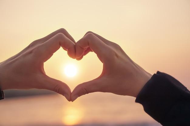 A mão da mulher faz a forma do coração no céu azul e no fundo do bokeh.