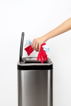 A mão da mulher joga uma máscara protetora e luvas de borracha na lata de lixo em um fundo cinza