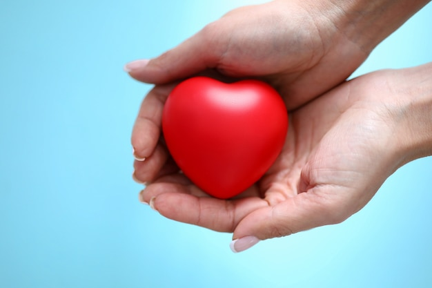A mão da mulher mantém o coração vermelho do brinquedo disponivel contra o close up azul do fundo. conceito de pessoas de caridade