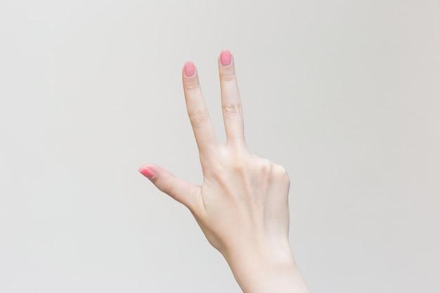 A mão da mulher mostra três dedos como o número três em fundo branco
