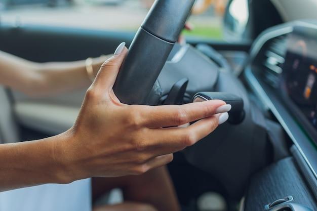 A mão da mulher muda os lóbulos do seletor de marcha no volante. a mão está trocando a alavanca de marcha do carro close up foto de um remo de mudança de marcha manual no volante de um carro