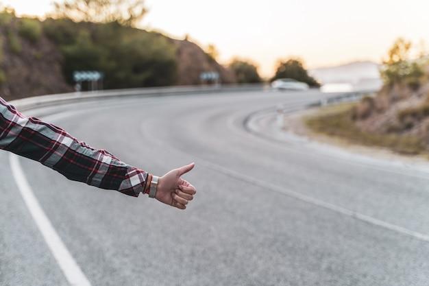 A mão da mulher pedindo carona na estrada à espera de um carro. conceito de exploração e aventuras.