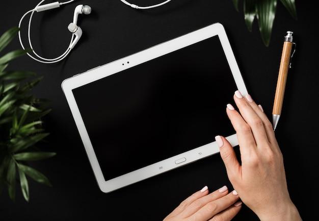 A mão da mulher plana leiga de vista superior segura um tablet com uma tela preta sobre uma bancada preta ao lado de uma caneta e fones de ouvido. conceito de espaço de trabalho de contabilidade doméstica. espaço de publicidade