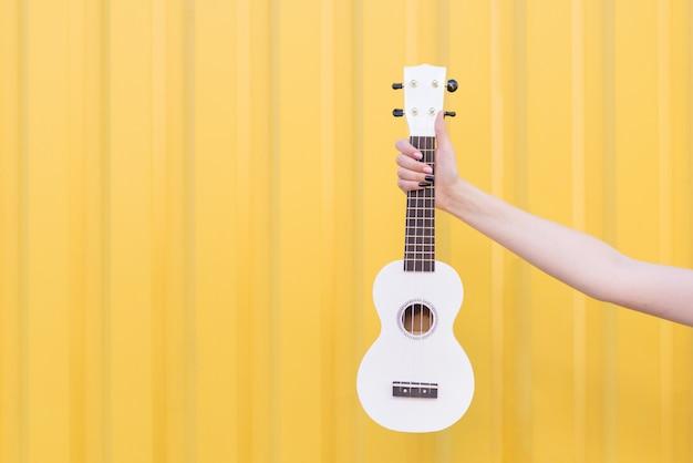 A mão da mulher prende a uquelele em uma parede amarela. conceito musical. música como hobby.