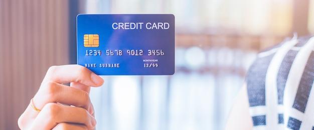 A mão da mulher prende um cartão de crédito azul.