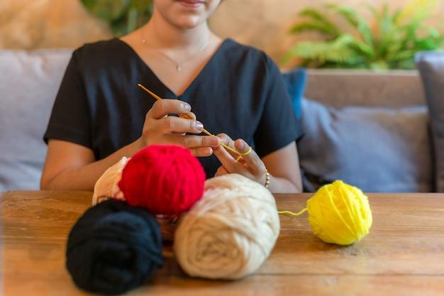 A mão da mulher que faz malha faz crochê em casa como o passatempo.