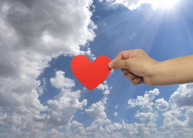 A mão da mulher que guarda um coração vermelho no fundo do céu.