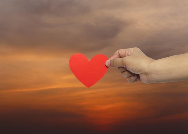 A mão da mulher que guarda um coração vermelho no fundo do por do sol.