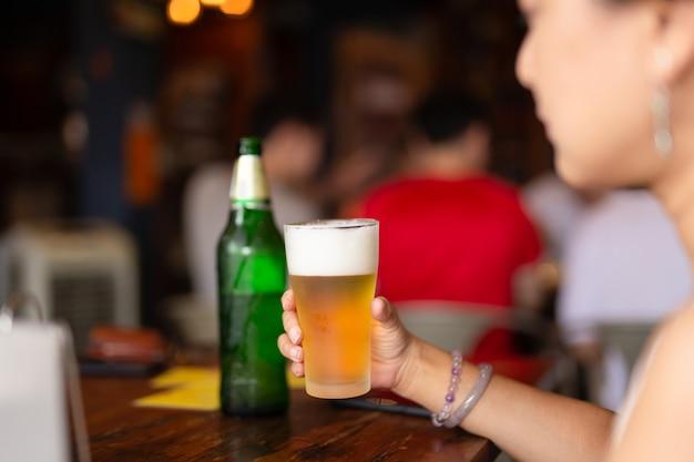A mão da mulher que guarda um vidro da cerveja fria em férias.