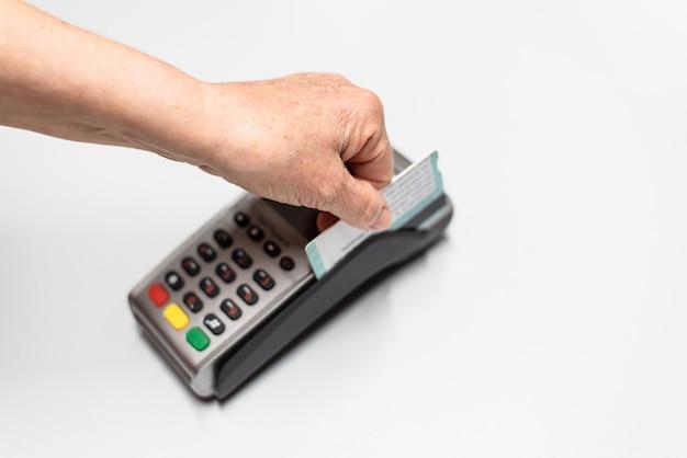 A mão da mulher que passa o cartão de crédito por um telefone de dados, leitor de cartão para carregar na época das vendas.