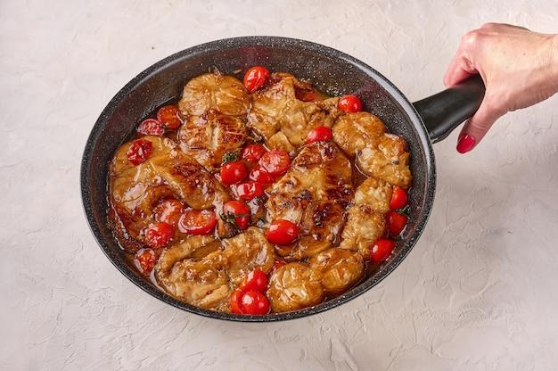 A mão da mulher segura a frigideira com o tradicional peixe siciliano com tomates e especiarias na luz