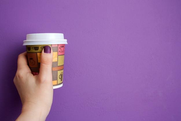 A mão da mulher segura levar café em frente à parede violeta