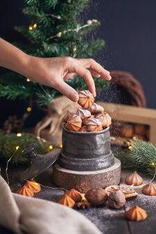 A mão da mulher segura o biscoito picci - biscoitos amanteigados de natal em frasco vintage no fundo de ramos de abeto.