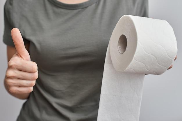 A mão da mulher segura o rolo do papel higiênico e mostra o polegar acima do gesto, fim. conceito de higiene