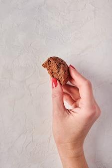 A mão da mulher segura um pedaço de bolinho na orientação vertical de foco seletivo de fundo claro de madeira
