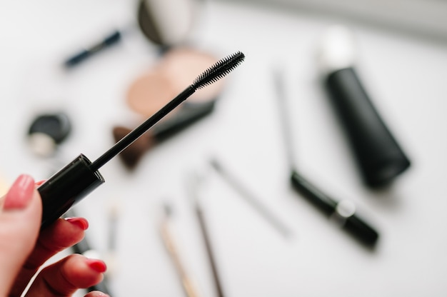 A mão da mulher segura um pincel para rímel em uma superfície borrada de diferentes cosméticos
