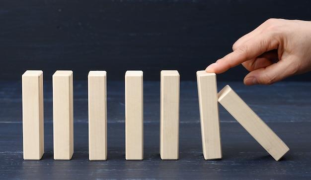 A mão da mulher segura uma barra e não permite que ela caia em uma fileira. conceito de seguro, um líder forte que impede a falência da empresa