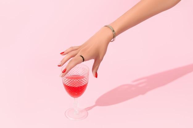 A mão da mulher segurando um copo no fundo rosa, tendências de design de manicure