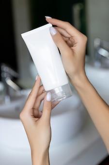 A mão da mulher segurando uma espuma de limpeza no banheiro