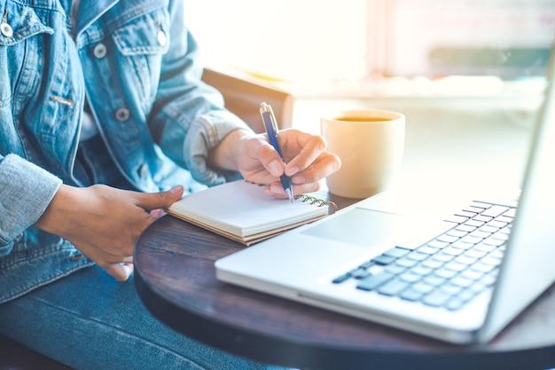 A mão da mulher usando o portátil e escrevendo no bloco de notas.