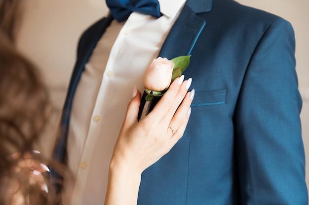 A mão da noiva prende uma flor rosa na jaqueta do noivo
