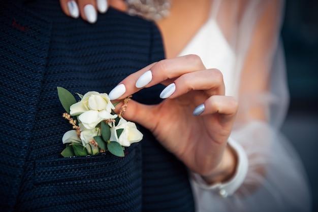 A mão da noiva toca a casa do botão da jaqueta do noivo
