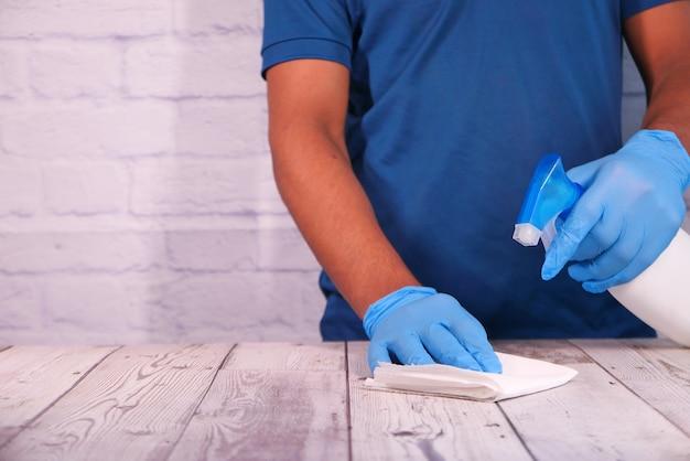 A mão da pessoa em luvas descartáveis usando spray desinfetante para limpar a superfície da mesa.