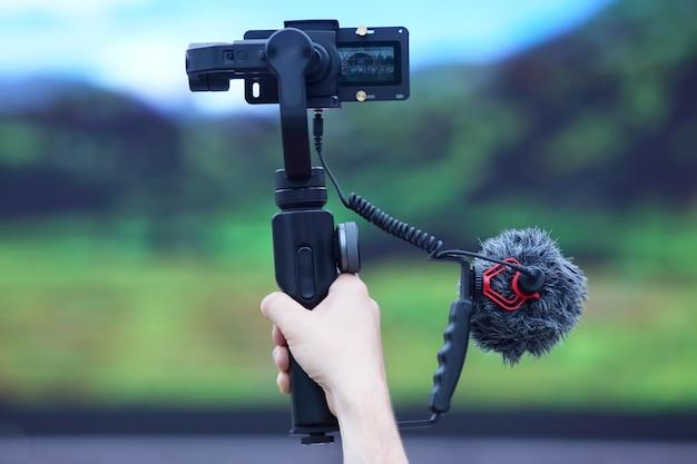 A mão da pessoa que filma o evento em uma câmera de vídeo com estabilizador. tecnologias e dispositivos modernos
