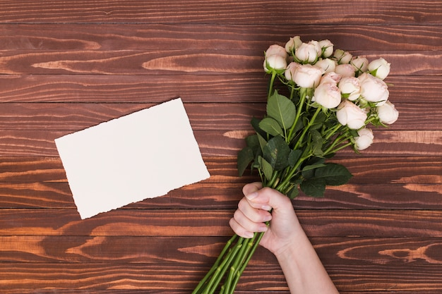 A mão da pessoa que guarda o grupo de rosas brancas; papel em branco sobre a mesa de madeira