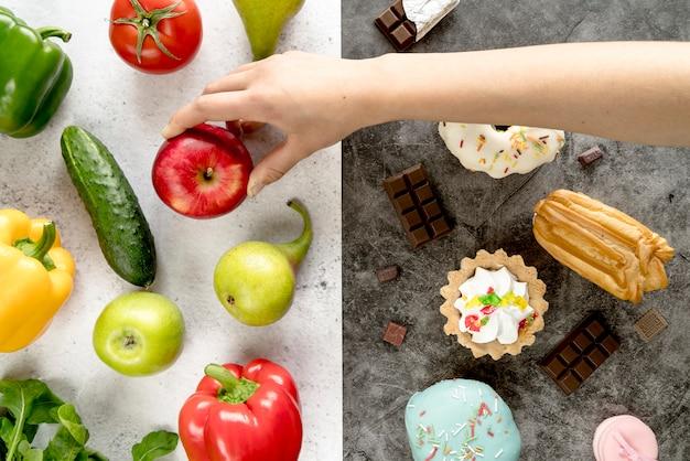 A mão da pessoa que toma a maçã da comida saudável