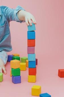 A mão das crianças está construindo uma torre de cubos coloridos de madeira.