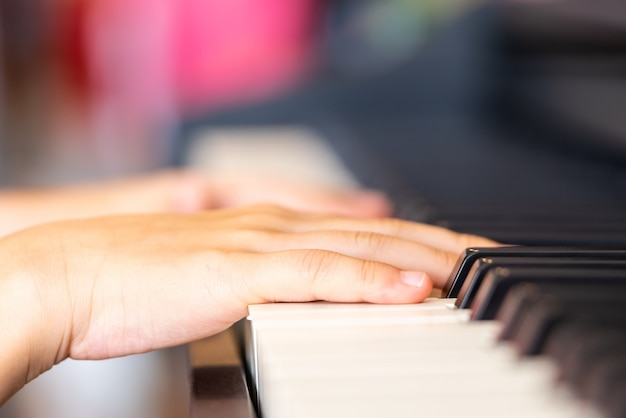A mão das crianças está jogando o piano do teclado da música