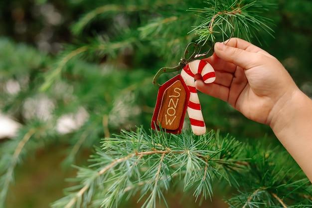 A mão das crianças pendura uma decoração em forma de bengala de doce na árvore de natal.