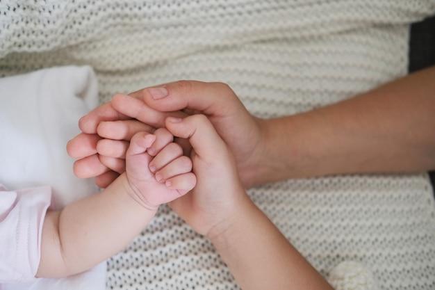 A mão das mães segura a mão do bebê e a mão das filhas. família feliz. aproveite o tempo juntos em casa. câmera lenta. ame. doce. ternura.