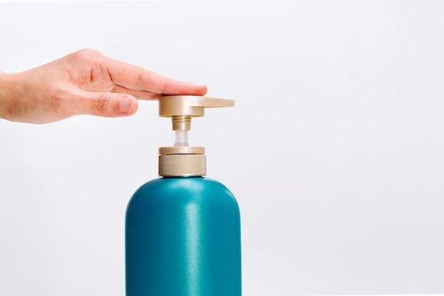 A mão das mulheres aplica a garrafa do condicionador do champô do cabelo no fundo branco.