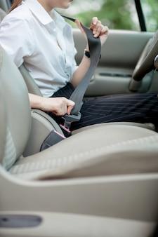 A mão das mulheres prende o cinto de segurança do carro.
