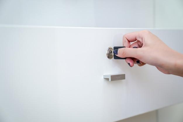 A mão das mulheres segurando a chave preta simples para abrir o guarda-roupa branco. fundo claro.