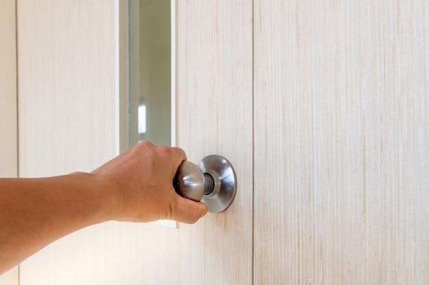 A mão das pessoas abre a porta para dentro, fora da porta aberta colocando na porta da frente