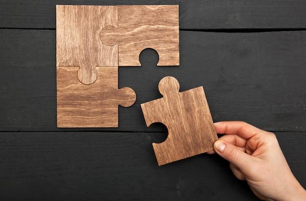 A mão de mulher conectando quebra-cabeças uns aos outros