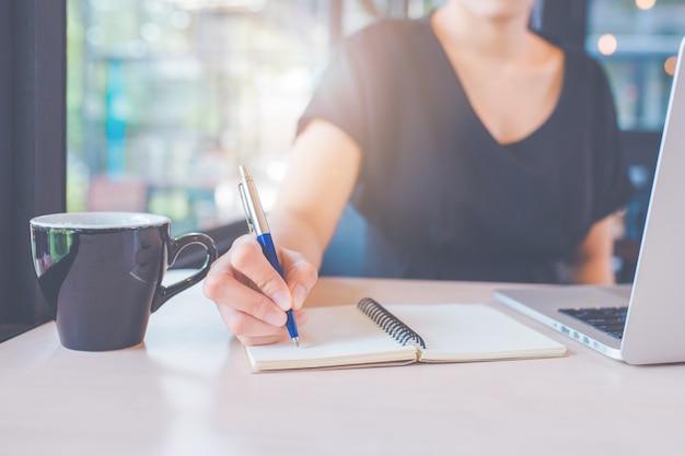 A mão de mulher de negócio está escrevendo em um caderno com uma pena.