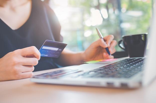 A mão de mulher de negócio prende um cartão de crédito e usa um computador portátil para comprar em linha.