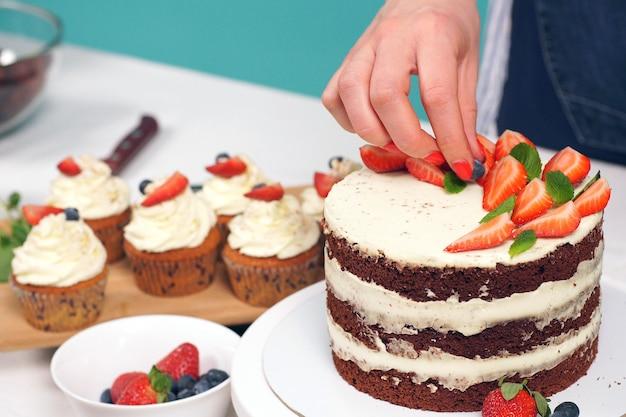 A mão de mulher decora um delicioso bolo de morango, close-up