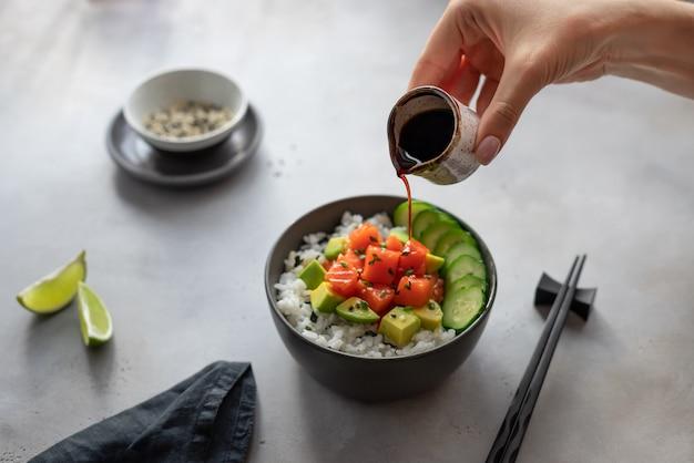A mão de mulher derrama molho de soja em uma tigela com salmão, arroz, abacate e pepino. tigela de puxão de conceito de comida.