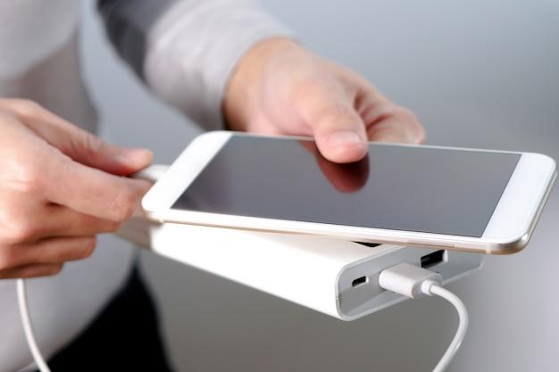 A mão de mulheres segurar o telefone e carregador, powerbank e telefone inteligente está se conectando